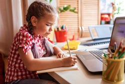 Distant education, back to school concept. Cute schoolchild studying homework during her online lesson at home, social distance during quarantine, self-isolation, communication via internet