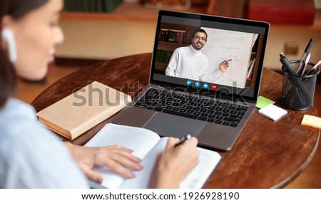 Distant Education Concept. Over the shoulder view of young woman wearing earbuds sitting at table and writing in her notebook, taking notes and using laptop, having online class
