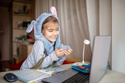 Distant education, online class meeting. Pretty schoolgirl wearing funny rabbit hat with ears to amuse classmates during boring online lesson at home, social distance during quarantine, self-isolation