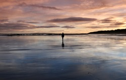 Distant figure alone on wet sands of a beach at sunset
