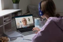 Distant lesson with middle-aged teacher. Adult grownup daughter or granddaughter talk with 60s grandmother use videocall, videoconference users, online meeting, over girl shoulder computer screen view