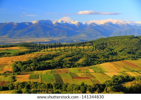 Distant mountains behind green hills under morning light #141344830