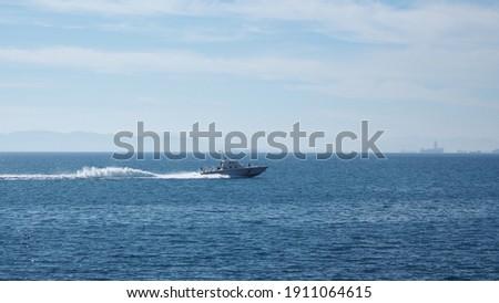 Distant photo of Hellenic coastguard speedboat cruising near port of Piraeus, Attica, Greece Stock foto ©