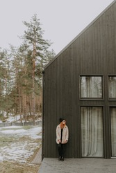 Distant portrait of young independent woman by her new bought house. Barn style modern gray wooden Scandinavian architecture. Woman happy to live alone. Feminism concept. Pink fashion coat in spring.