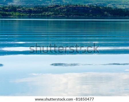 Distant shoreline, clouds and blue sky mirrored on calm lake surface with distortions of some ripples.