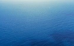 Distant shot of sea with ripples. There is a tiny boat near the horizon.