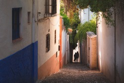 Distant silhouette figures and early morning golden light over the quiet and quaint narrow cobblestone streets in old town (Albaicin or Arab Quarter) Granada, Spain, Andalusia.