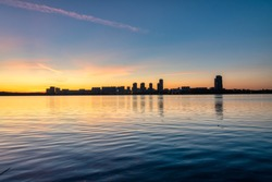 Distant silhouette of urban buildings against the backdrop of the sunset reflected in the water of the bay
