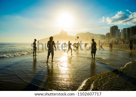 Distant sunset silhouettes playing keepy-uppie beach football on the sea shore in Ipanema Beach Rio de Janeiro Brazil Foto stock ©