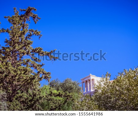 distant view of Athena Nike ancient temple between trees and clear blue sky, Athens Greece