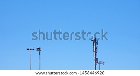 Distant view of the tops of two tall floodlight lamps and a telephone communication tower with bright blue sky behind #1456446920