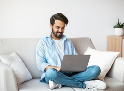 Distant Work. Happy Arab Freelancer Man Using Laptop Computer At Home, Typing On Keyboard, Young Eastern Guy Sitting On Sofa In Living Room, Working Remotely On Online Project, Copy Space