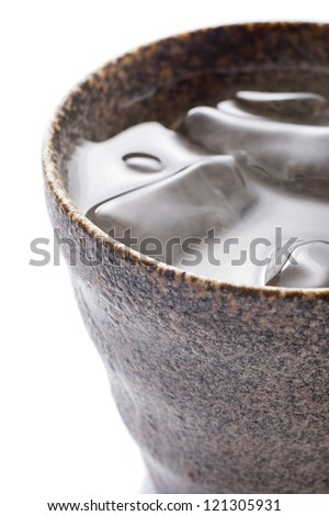 Distilled spirit into the pottery cup on white background