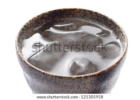 Distilled spirit into the pottery cup on white background - stock photo