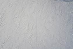 Distinct imprint of snowmobile / endless track path into the distance on clean snow field on small mount at winter sunny frozen day - Aerial drone view