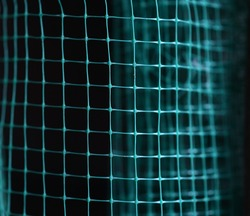 distorted green wireframe grid on dark background, abstract background. Selective focus.