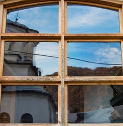 Distorted reflection of the dome of a church in the glass of a wooden window. A church is reflected in the glass of the window. Blue sky with clouds