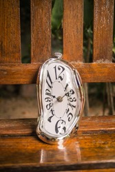 Distorted soft melting clock on a wooden bench, the Persistence of Memory of Salvador Dali