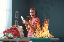 Distracted careless housewife chatting with her phone, she is burning clothes with the iron