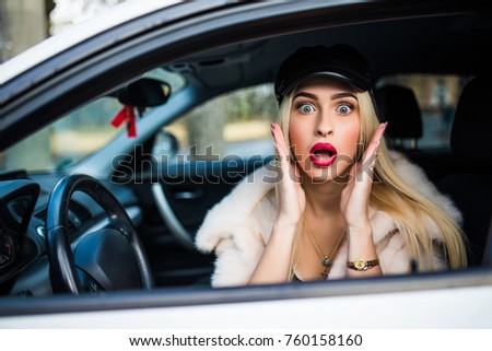 Distracted fright face of a woman driving car, wide open mouth eyes holding wheel side window view. Negative human face expression emotion reaction. Trip risk danger reckless behavior on road concept