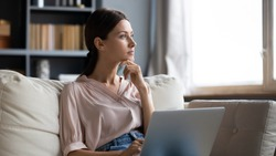 Distracted from work worried young woman sitting on couch with laptop, thinking of problems. Pensive unmotivated lady looking at window, feeling lack of energy, doing remote freelance tasks at home.
