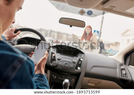 Distracted young male driver looking at the screen of his mobile phone while running over a pedestrian. Technology and transportation concept. Selective focus on hand with smartphone. Horizontal shot Foto stock ©