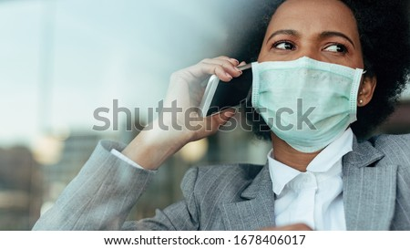Distraught black businesswoman communicating over smart phone while wearing face mask during virus epidemic. The view is through the glass.