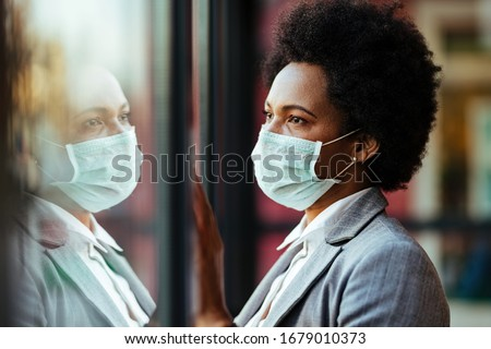 Distraught black businesswoman wearing protective mask while standing by the window and looking through it.
