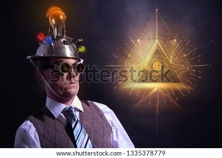 distraught looking conspiracy believer in suit with aluminum foil head and illuminati sign