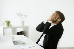 Distraught stressed businessman in suit covers face with hands feeling despair after business failure online sitting at work desk with laptop, frustrated hopeless entrepreneur shocked by bankruptcy