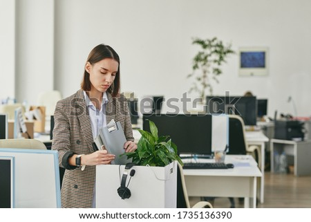 Distraught young woman in checkered jacket packing stuff after dismissal in coronavirus crisis