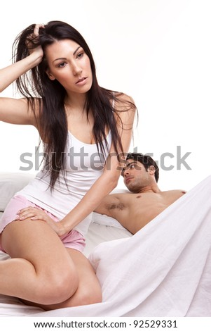 Distraught Young Woman On Bed with her husband lying behind, studio on white