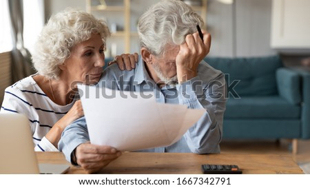 Distressed mature 60s husband and wife sit at table calculate manage household expenses having problems with finances, upset pensioners frustrated troubled with paying bills expenditures