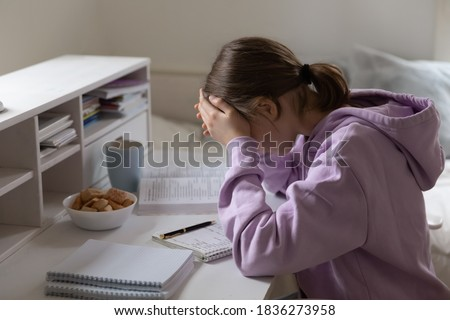 Distressed teen 13s girl pupil feel unmotivated studying alone doing homework at home. Upset unhappy teenage child stressed with school task assignment preparation, have difficulties with learning. Photo stock ©