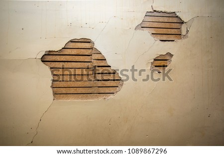 Distressed wall with holes in plaster and wood lath.