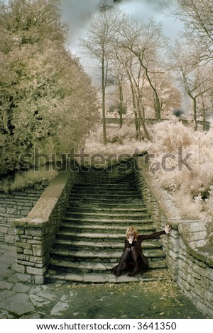 Distressed woman on stone steps in infrared.