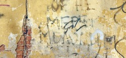 Distressed Yellow Brown Old Brick Wall With Graffiti. Street Art Background And Wide Cracked Texture. Damaged Concrete Wall With Painted Lines And Draw. Abstract Rough Grafitty Wallpaper. Web Banner
