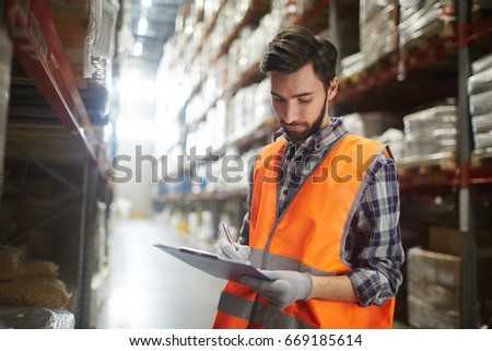 Distribution manager making revision of goods in storehouse #669185614