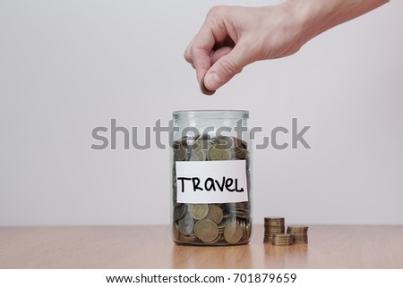 Distribution of cash savings concept. Hand puts coins to the glass money boxes with inscription 'travel' #701879659