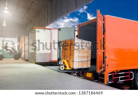 Distribution warehouse and Logistics, freight transportation. Forklift loading cargo into a truck, trucks docking standby load the shipment. #1387186469