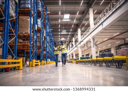 Distribution warehouse interior with workers wearing hardhats and reflective jackets walking in storage area.