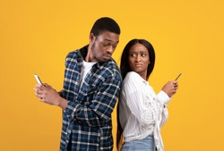 Distrust, jealousy, online media and personal space. Interested young african american student guy in casual looks at wife smartphone, lady hides gadget, isolated on yellow background, studio shot
