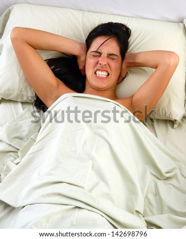 Disturbed woman lying down on bed trying to sleep.
