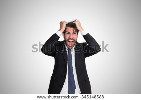 Shutterstock Disturbed young business man going wild by pulling his hair, on gray background.