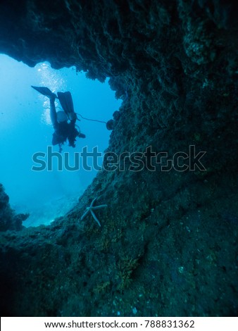 Diver dive pass through a hole in underwater cave #788831362