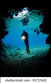 Stock Photo: Diver in front of an underwater cave