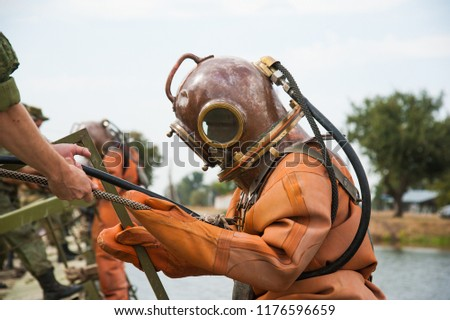 Diver immerses in a copper old vintage deep sea diving suit #1176596659