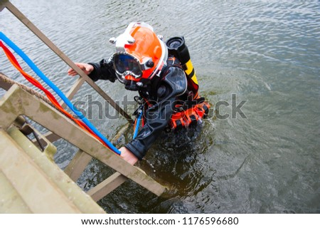 Diver in the water in a diving suit and helmet ready to dive #1176596680