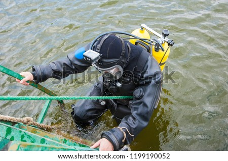 Diver in the water in a diving suit and helmet ready to dive #1199190052
