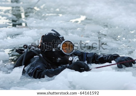 Diver rising on the surface between the ice